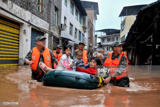 This photo taken on June 28, 2020 shows rescuers evacuating residents in a flooded area after heavy rain in China's southwestern Chongqing. -...
