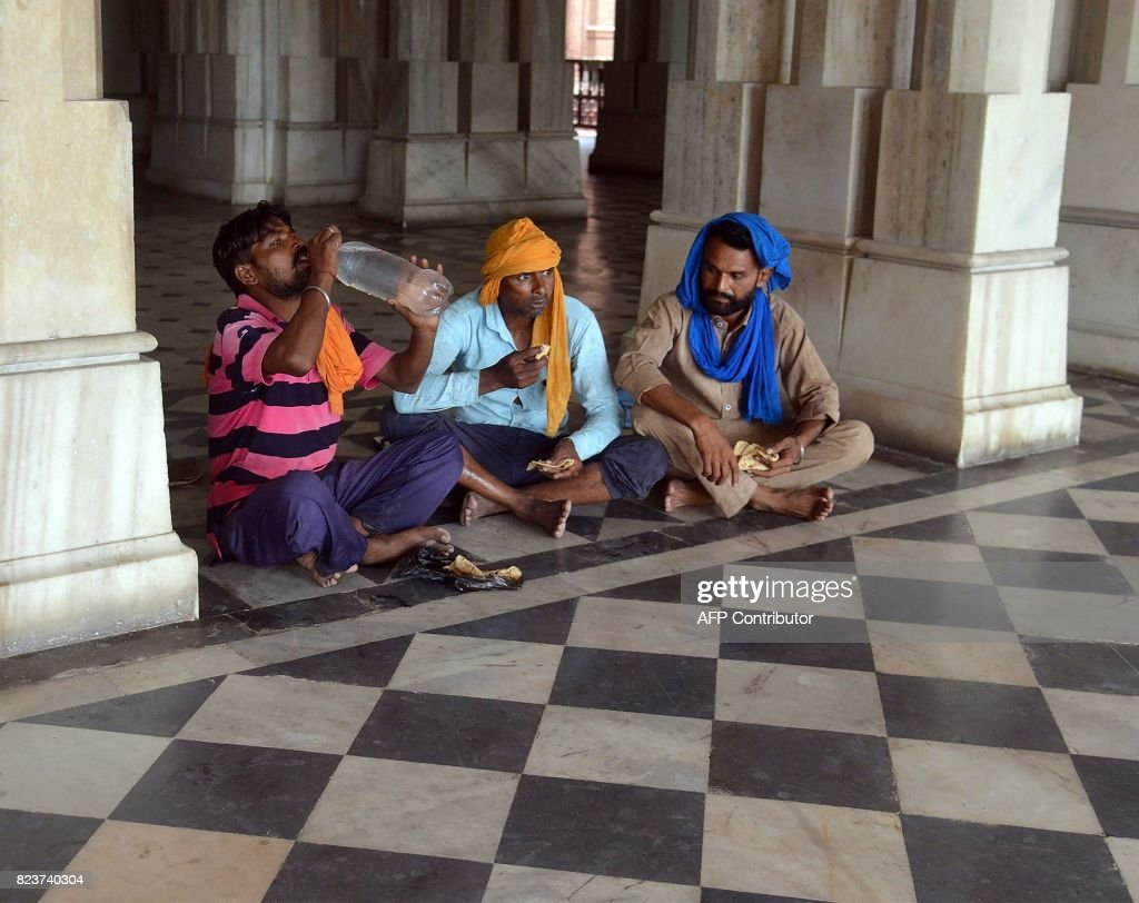 This photo taken on June 29 2017 shows Indian labourers eating food at Khalsa College in Amritsar In August 1947 the British Raj was dismantled...