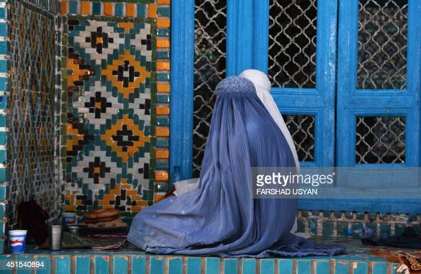 This photo taken on June 30 2014 shows Afghan burqaclad women waiting to break their fast during the holy month of Ramadan at the Hazrate Ali shrine...
