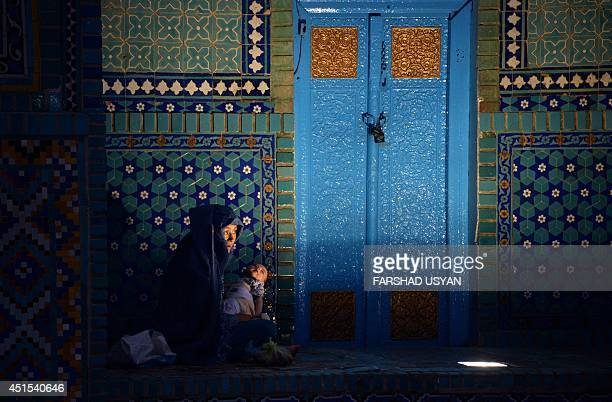 This photo taken on June 30 2014 shows an Afghan burqaclad woman waiting to break fast during the holy month of Ramadan at the HazrateAli shrine or...