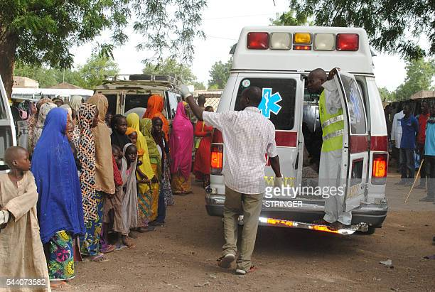 This photo taken on June 30 2016 shows displaced children L watching as malnurished and sick children are being taken away in an ambulance for...
