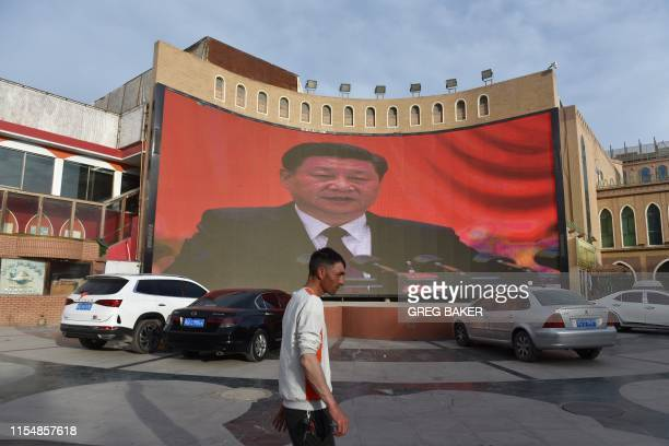 This photo taken on June 4, 2019 shows a man walking past a screen showing images of China's President Xi Jinping in Kashgar in China's northwest...