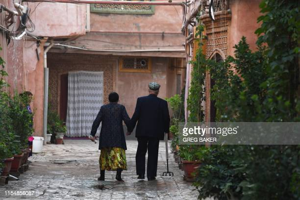 This photo taken on June 4, 2019 shows a Uighur couple walking in a restored section of the old city in Kashgar in China's northwest Xinjiang region....
