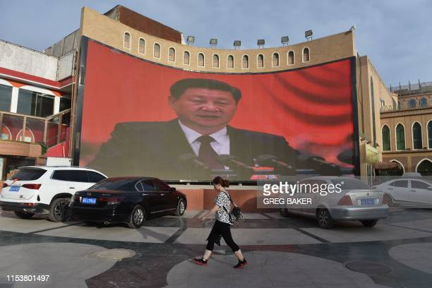 This photo taken on June 4 2019 shows people walking past a screen showing images of Chinese President Xi Jinping in Kashgar in China's western...