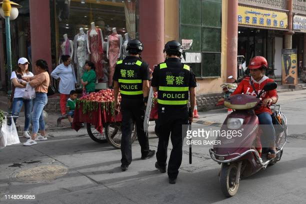 This photo taken on June 4 2019 shows police officers patrolling in Kashgar in China's western Xinjiang region While Muslims around the world...