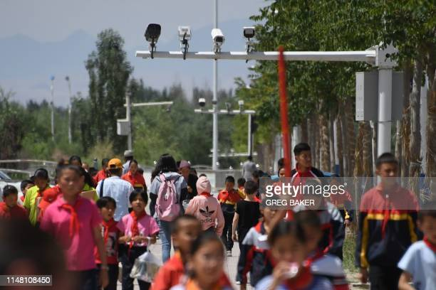 This photo taken on June 4 2019 shows schoolchildren walking below surveillance cameras in Akto south of Kashgar in China's western Xinjiang region...