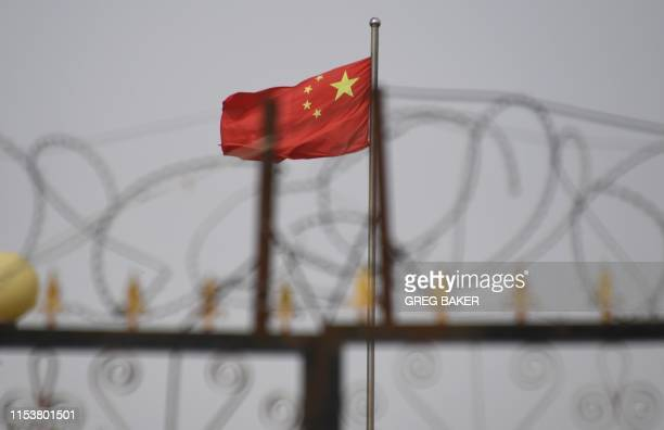 TOPSHOT This photo taken on June 4 2019 shows the Chinese flag behind razor wire at a housing compound in Yangisar south of Kashgar in China's...