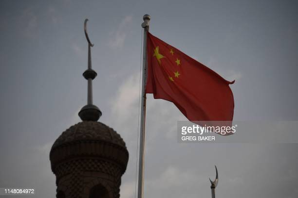 This photo taken on June 4 2019 shows the Chinese flag flying over the Juma mosque in the restored old city area of Kashgar in China's western...