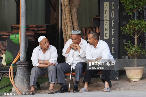 This photo taken on June 4, 2019 shows Uighur men resing in front of a coffee bar in the restored old city area of Kashgar, in China's western...
