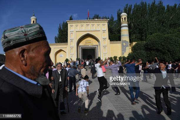 This photo taken on June 5, 2019 shows Uighur men dancing after Eid al-Fitr prayers, marking the end of Ramadan, outside the Id Kah mosque in...