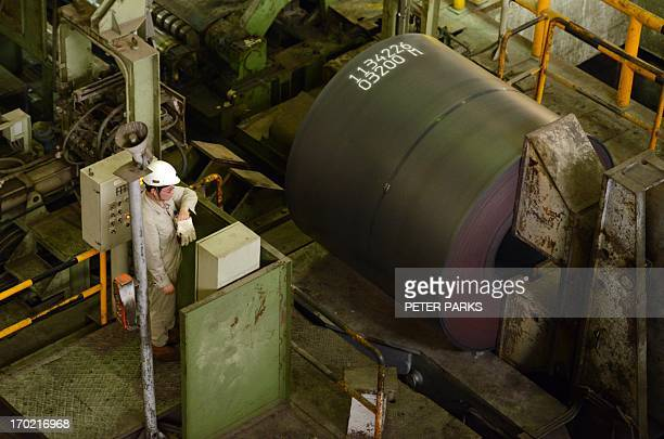 This photo taken on June 6 2013 shows a worker loading a roll of steel at the hot rolling plant at the Baosteel steel mill in Shanghai during a tour...