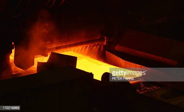 This photo taken on June 6 2013 shows red hot steel being flattened in the hot rolling plant at the Baosteel steel mill in Shanghai during a tour of...
