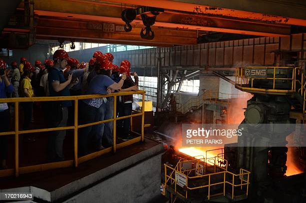 This photo taken on June 6 2013 shows visitors watching the hot rolling process at the Baosteel steel mill in Shanghai during a tour of the plant...