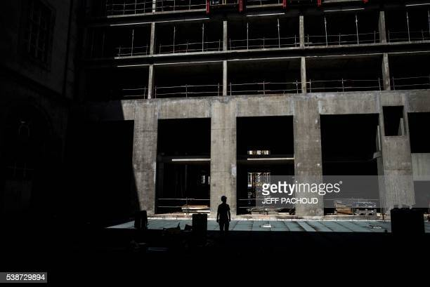 This photo taken on June 7, 2016 shows an employee of Eiffage Construction group working in the yard of the Hotel Dieu in Lyon. The renovation of the...