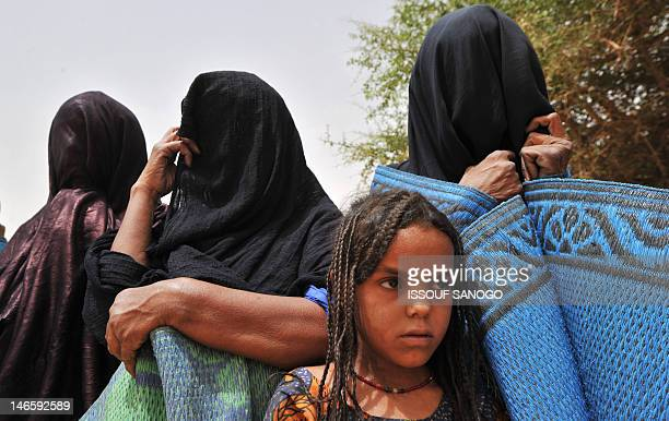 This photo taken on June 8, 2012 during a traditional ceremony, in a village near Abalak, shows a child and veiled Tuareg women wrapped in rugs to...
