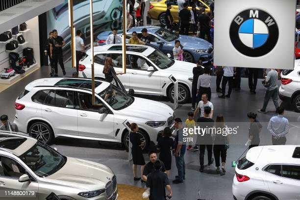 This photo taken on June 8, 2019 shows people looking at BMW cars in the 18th Shenyang, International Automobile Industry Expo in Shenyang, in...