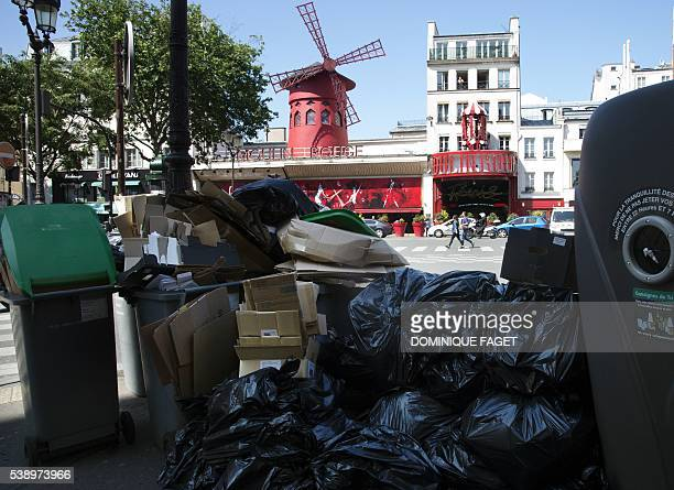 This photo taken on June 9 2016 in Paris shows a pile of garbage next to the Moulin Rouge cabaret On June 9 one day before the start of Euro 2016 in...