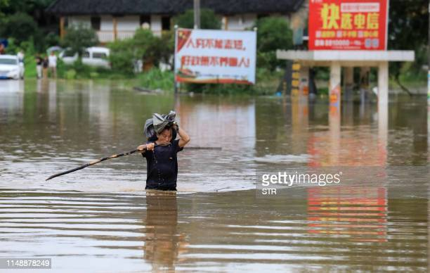 This photo taken on June 9 2019 shows a man wading through floodwater in Rongan in China's southern Guangxi region after heavy rainstorm hit the area...