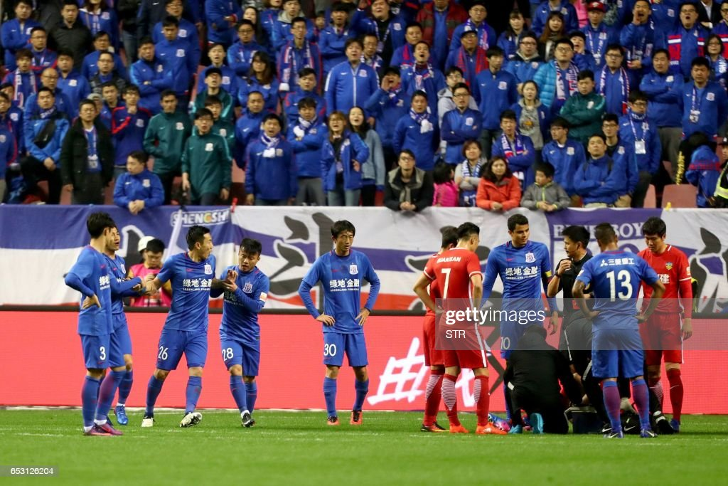 This photo taken on March 11, 2017 shows Shanghai Shenhua's Qin Sheng (26) leaving the pitch after being given a red card during the Chinese Super League match against Tianjin Quanjian in Shanghai. Shanghai Shenhua will withhold the salary of China international Qin Sheng for the rest of the season after condemning the midfielder's 'abominable behaviour' in stamping on Belgium's Axel Witsel at the weekend. / AFP PHOTO / STR / China OUT