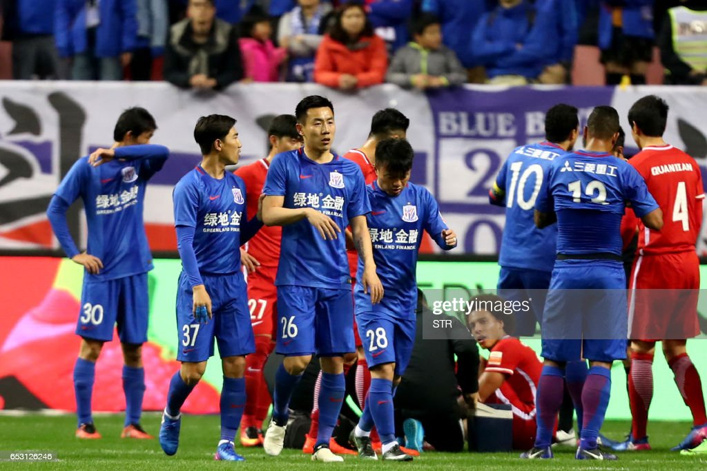 This photo taken on March 11, 2017 shows Shanghai Shenhua's Qin Sheng (26) leaving the pitch after being given a red card during the Chinese Super League match against Tianjin Quanjian in Shanghai....