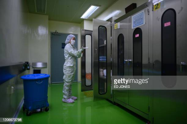 This photo taken on March 11, 2020 shows Animal Research Facility supervisor Kim Seung-yeon putting on protective clothing required to enter a...