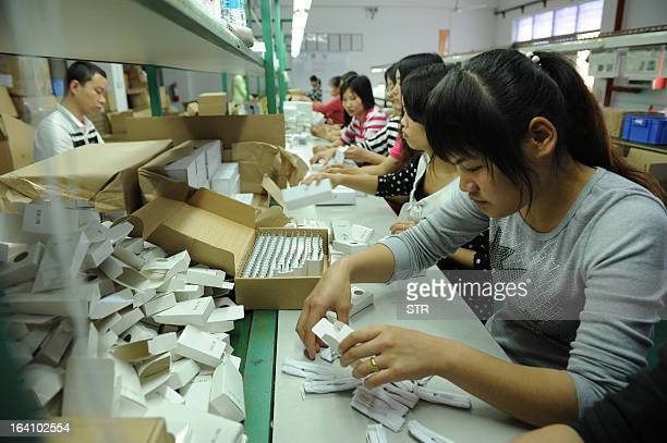 This photo taken on March 12 2013 shows Chinese workers packing electronic cigarettes at a factory in Shenzhen in southern China's Guangdong province...