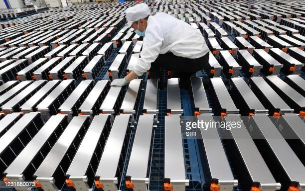This photo taken on March 12, 2021 shows a worker with car batteries at a factory for Xinwangda Electric Vehicle Battery Co. Ltd, which makes lithium...