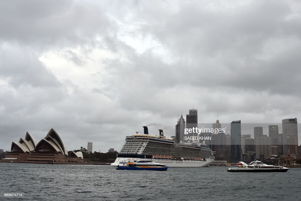 This photo taken on March 13, 2017 shows a cruise ship leaving Sydney harbour as storm clouds cover the sky