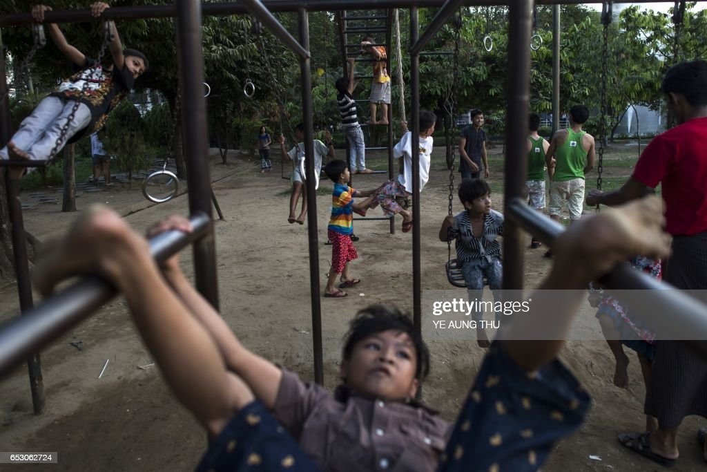 This photo taken on March 13, 2017 shows children playing in a park in downtown Yangon. / AFP PHOTO / Ye Aung THU