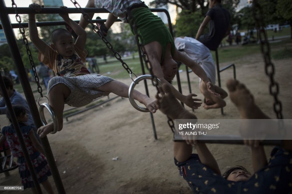 This photo taken on March 13, 2017 shows children playing in a public park in downtown Yangon. / AFP PHOTO / Ye Aung THU