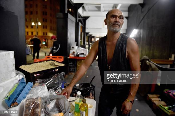This photo taken on March 13 2017 shows homeless man Lanz Priestley preparing food in a makeshift shelter for the homeless in Sydney which offers...