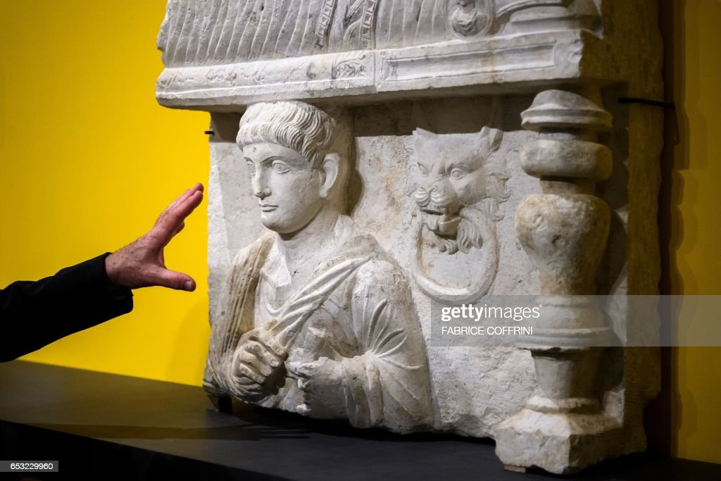 This photo taken on March 14, 2017 at Geneva's Museum of Art and History shows a funeral bas-relief from Palmyra, Syria, discovered during a custom control on April 2013 in the Geneva Freeport warehouse complex, during an exhibition on the illegal trafficking of archaeological objects before being returned. Geneva's Museum of Art and History displays for several months nine cultural relics looted from Syria's ancient city of Palmyra, as well as from Libya and Yemen, which were being stored in Geneva's Freeport warehouse complex and seized by the Canton of Geneva. The objects will be on display from March 14 until September 30 of 2017. PHOTO / Fabrice COFFRINI / RESTRICTED