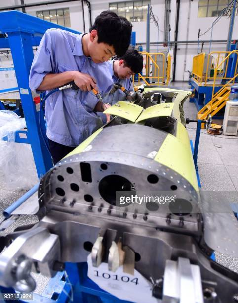 This photo taken on March 14 2018 shows Chinese employees working on an engine part of China's homegrown C919 passenger jet at a factory in Shenyang...