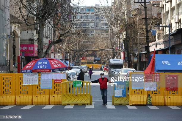 This photo taken on March 15 2020 shows a volunteer standing at a barrier set up to prevent people from entering or leaving a community in Wuhan in...