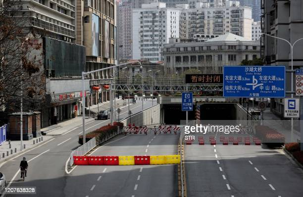 This photo taken on March 15 2020 shows barriers set up to block off a street in Wuhan in China's central Hubei province After Wuhan and its 11...