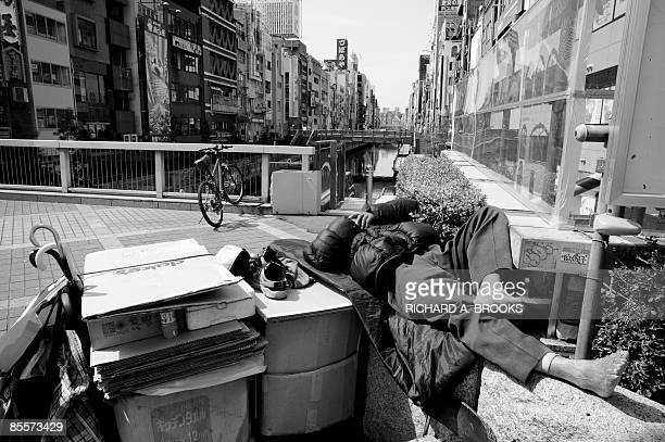 This photo taken on March 16 2009 shows a homeless man sleeping at midday above the Dotonbori canal area in the western Japanese metropolis of Osaka...