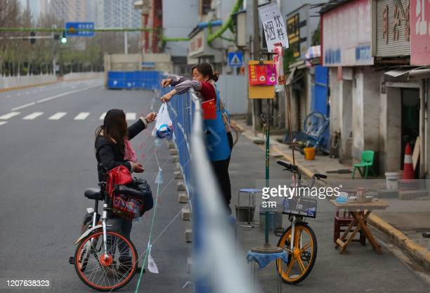 TOPSHOT This photo taken on March 16 2020 shows a woman delivering food to a resident over a barrier set up to prevent people from entering or...