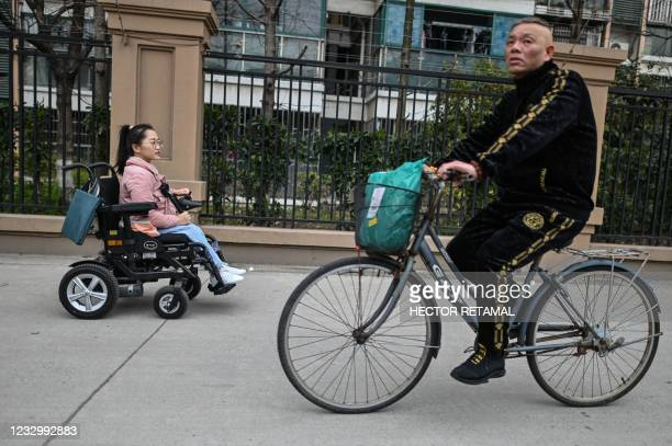 This photo taken on March 17, 2021 shows video blogger Zhao Hongcheng along a street on her way to work in Shanghai. - Busy, narrow or clogged...
