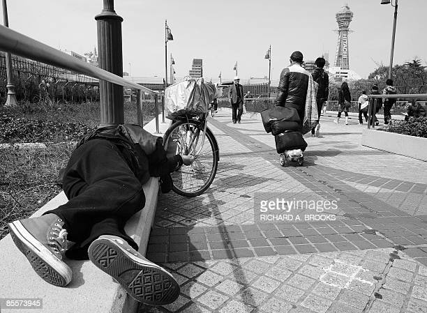 This photo taken on March 18 2009 shows a homeless man walking past another man sleeping near Tennoji Park in the western Japanese metropolis of...