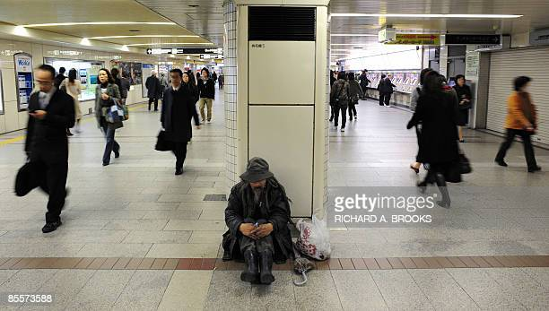 This photo taken on March 18 2009 shows commuters walking past a homeless man sitting inside a train station in the western Japanese metropolis of...