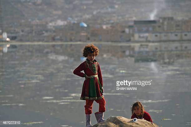 This photo taken on March 18 2015 shows two Afghan girls playing near polluted Shuhada Lake in Kabul A new UN report launched in New Delhi on March...