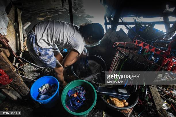 This photo taken on March 18 2020 shows a mother washing laundry outside her home along the river in Manila Asian nations have imposed increasingly...
