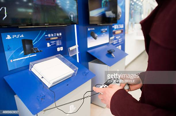 This photo taken on March 19 2015 shows a man playing with a Sony PlayStation 4 in a shop in downtown Shanghai After a twomonth delay Japanese...