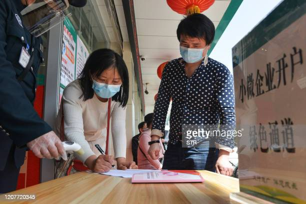 This photo taken on March 19, 2020 shows a customer filling in her information before entering a bank in Yunmeng county, in Xiaogan City in China's...