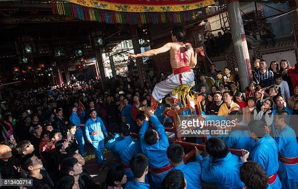 This photo taken on March 2 2016 shows a young man flaying his back with a thorny iron during the 'Da Tiequ' event in front of the Dalugong Temple in...