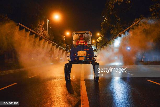 This photo taken on March 2 2020 shows a worker spraying disinfectant on a road in Yunmeng county Xiaogan city in China's central Hubei province The...
