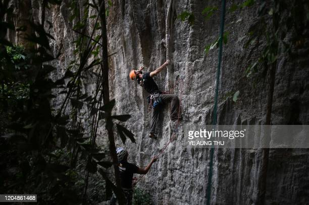 This photo taken on March 2 2020 shows climbers Andrew Railey and Nyi Nyi working on the development of new sport climbing routes in Hpa An Karen...
