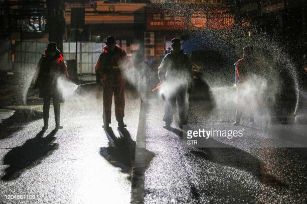TOPSHOT This photo taken on March 2 2020 shows workers spraying disinfectant on a road in Yunmeng county Xiaogan city in China's central Hubei...