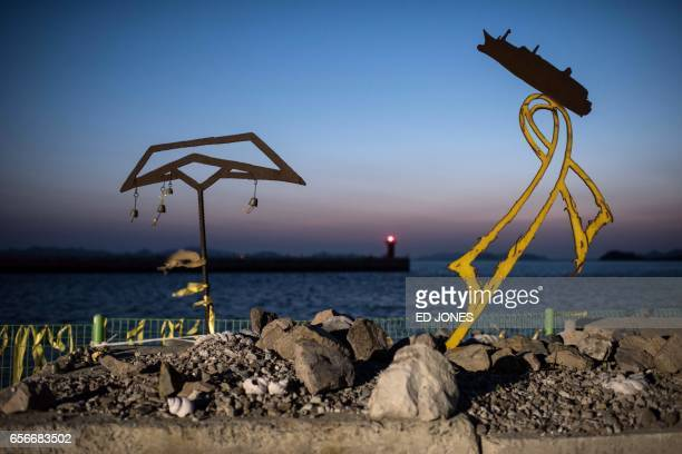 TOPSHOT This photo taken on March 21 2017 shows memorials displayed near makeshift homes at Paengmok harbour where a group of relatives of nine...