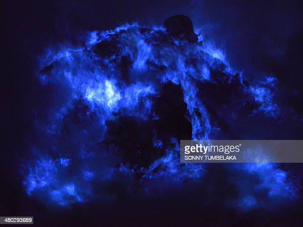 This photo taken on March 22 2014 shows the blue flame of burning sulfur at the crater of the Kawah Ijen volcano in Banyuwangi regencyEast Java...